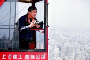 Crane operator Wei Gensheng in his crane over Shanghai, China.