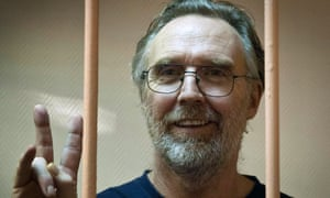 "Greenpeace International activist Colin Russell from Australia flashing the V-sign for ""victory"" while standing in a defendant cage in a court in Russia's second city of Saint Petersburg"