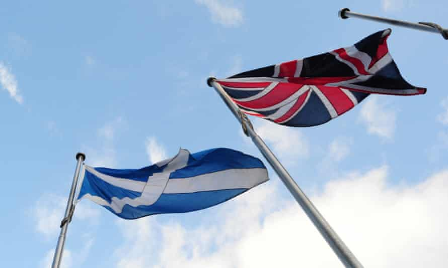 The Scottish saltire and the union flag fly side by side outside the Scottish Parliament. Science spending in Scotland may be threatened by English policy mistakes.
