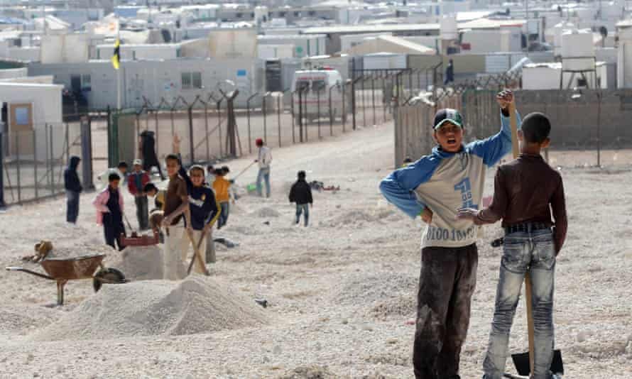 Syrian refugee children help move small stones for their tents in Zaatari refugee camp, Jordan