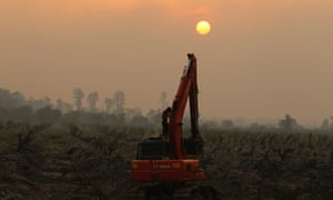A worker washes himself on an excavator at a palm oil plantation near Dumai, as haze from clearance fires covers Indonesia's Riau province June 20, 2013. Demand for biofuel from palm oil and other crops has been blamed for creating secondary land clearance and increasing greenhouse gas emissions.