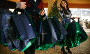 Tommy Hilfiger employees give away tote bags to shoppers