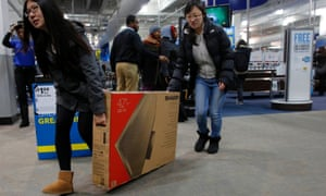 Two women slide a newly purchased television to the door at a Best Buy store