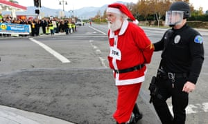 Walmart protester Karl Hilgert, dressed as Santa Claus, is led away after being arrested for failure to disperse after sitting down with nine other protesters in the middle of an intersection in Ontario, Calif.