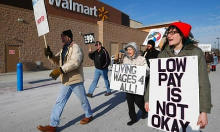 A group of protesters walk through the Walmart retail store parking lot on Black Friday in Elgin, Illinois, November 29, 2013.