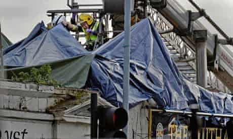 Rescue workers beside the wrecked helicopter on the roof of the Clutha bar in Glasgow