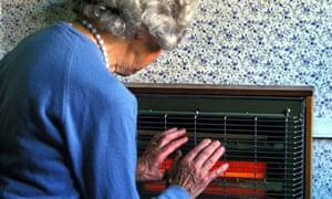 An old woman holding her hands near an electric fire