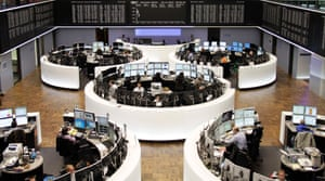 Traders are pictured at their desks in front of the DAX board at the Frankfurt stock exchange November 4, 2013.