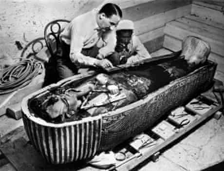 Howard Carter examines the sarcophagus containing the body of the pharaoh Tutankhamun in the Valley of the Kings