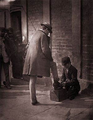 Street Life in London: A young independent shoeblack shines the boots of a city gent