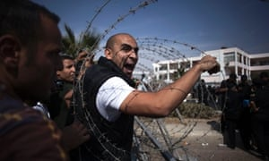 A supporter of Egypt's ousted President Mohammed Morsi shouts to a police officer outside of a police academy compound were the trial of ousted President Mohammed Morsi is held in Cairo, Egypt.