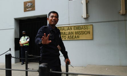 A security personnel raises his hand in an attempt to stop the media from taking pictures in front of the Australian Embassy gate in Jakarta.