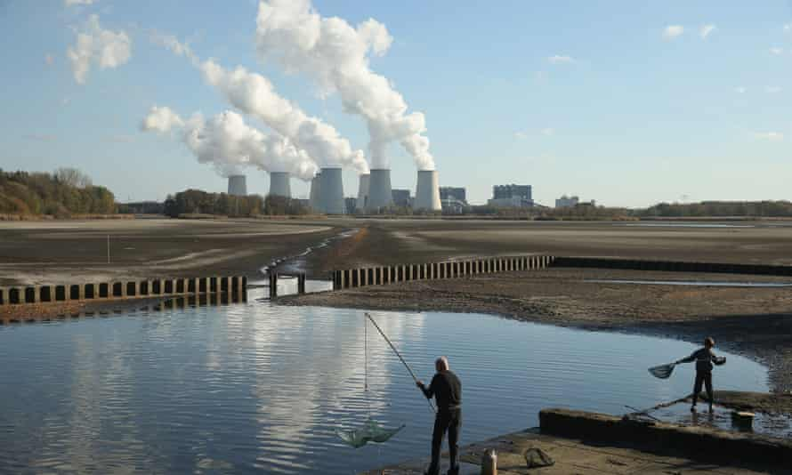 PEITZ, GERMANY - OCTOBER 31:  Fishermen cast nets as the cooling towers of the Jaenschwalde coal-fired power plant loom behind on October 31, 2013 in Peitz, Germany