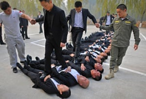 Trainees walk over the bodies of their fellow trainees at a bodyguard training camp in Beijing.