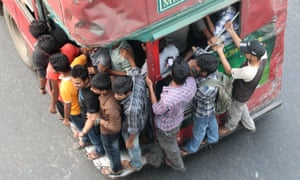 People cram onto buses packed buses in Dhaka, Bangladesh