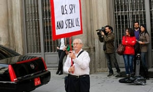 Man holds banner outside Madrid meeting between foreign ministry and the US ambassador to Spain