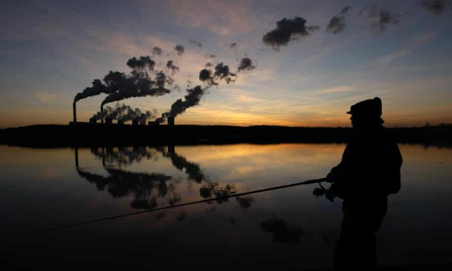 A man fishes in an artificial lake outside Belchatow Power Station, Europe's largest coal-fired power plant, October 31, 2013.
