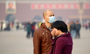 A man wears a face mask in the smog as another visitor covers her mouth during a visit to Tiananmen Square in Beijing.
