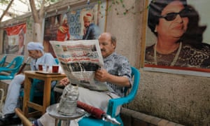 An Egyptian man reads the daily Al-Ahram newspaper with the trial of Egypt's ousted President Mohammed Morsi on the front at a coffee shop in Cairo.