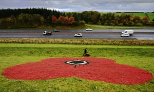 Joe Campbell walks his dog past a giant poppy painted on the side of the Bathgate Pyramids ahead of Remembrance Sunday and Armistice Day in Glasgow, Scotland.