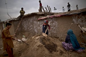 A displaced Pakistani family fixes the rooftop of their mud house in preparation for the rain season, in Islamabad, Pakistan.
