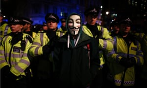 A protester wearing a Guy Fawkes mask stands in front of a line of riot police officers during a protest against budget cuts and energy prices in Westminster, central London.