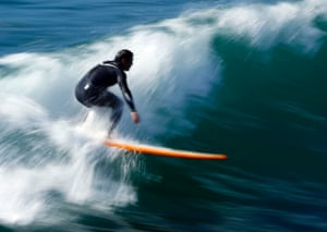 A surfer catches a wave off the coast of Oceanside, California, United States.
