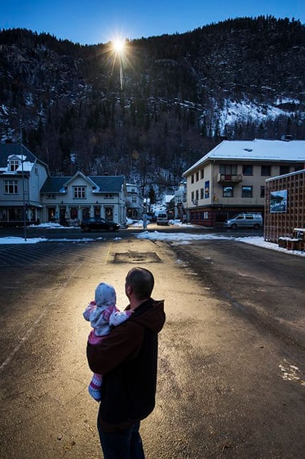 A man holds his baby up to the light reflected by the mirrors.