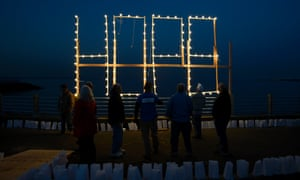 Residents look up at the word 'Hope' in lights during a community ceremony marking the one year anniversary of Hurricane Sandy in Union Beach, New Jersey, USA, 29 October 2013