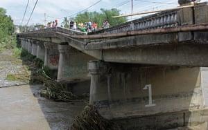 Typhoon Aftermath: People look at a damaged bridge