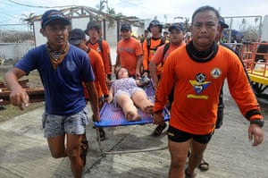 Typhoon Haiyan: Rescue workers carry a woman a