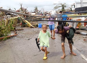 Typhoon Haiyan: A mother and her son walk under damaged electric cables