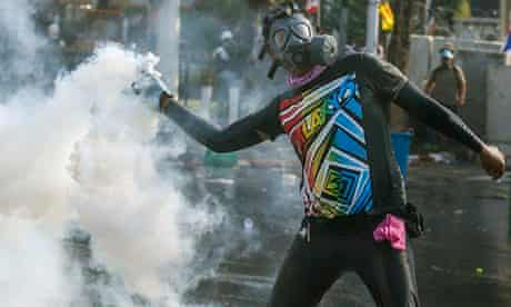 An anti-government protester throws back a teargas canister during clashes with police in Bangkok