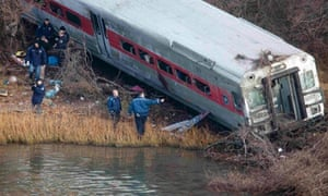 Emergency workers examine the site of a Metro-North train derailment in the Bronx borough of New York December 1, 2013. At least four people were killed and 63 injured, including 11 critically,