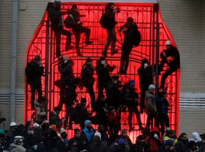 Ukraine protests: Protesters climb the gate of a building in Kiev