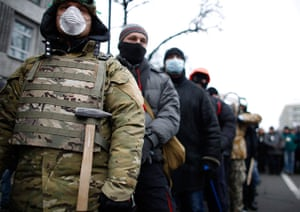 Ukraine protests: Demonstrators wear masks as they attend the rally