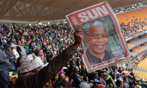 A man  holds up an image of former South African president Nelson Mandela ahead of a memorial service at the FNB Stadium.