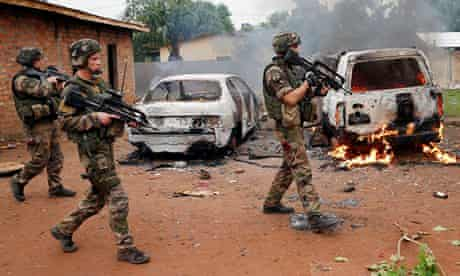 French troops patrol past two rebel vehicles set on fire in Bangui, Central African Republic