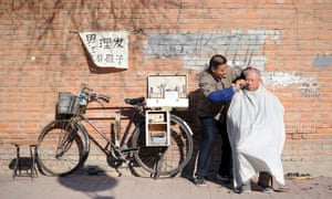 A barber cuts the hair of a customer on a road in Beijing, China.