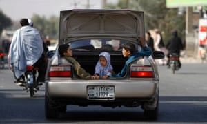 Afghan children ride in the boot of a car in Kandahar, Afghanistan.