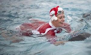Woman swimming dressed as Santa