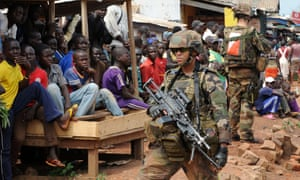Young people watch as French soldiers of the Sangaris operation patrol in the North of Bangui, Central African Republic. Two French soldiers have been killed on the second day of an operation to disarm fighters sowing sectarian violence in the country.