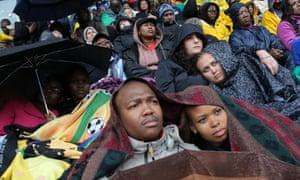 People shelter under blankets during the memorial service for former Mandela.