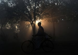 A Pakistani milkman rides a bicycle on foggy day in Lahore.