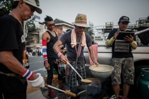 Anti-government protesters cook dinner outside the Government House in Bangkok, Thailand. Prime Minister Yingluck Shinawatra refused demands by anti-government protesters that she resign before upcoming elections.