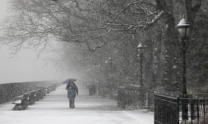 A person walks on a deserted walkway on a snowy morning in New York, US.