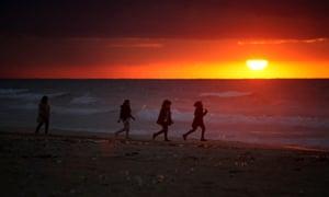 Girls walk on the shore  beach in Gaza City at sunset.
