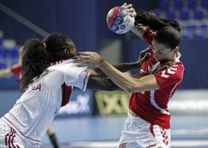 Polands Kinga Grzyb (R) vies with Angola's Isabel Evelize Wangimba Guialo during the Women's Handball World Championship 2013 match Poland vs Angola in Zrenjanin, Serbia.