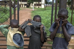 Children protect their noses as they stand outside the morgue of Bangui's hosptial in Central African Republic.