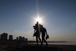 Two swimmers walk along a beach next to the Amazon River at sunrise in Manaus, Brazil. Manaus will play host to four FIFA World Cup soccer matches next summer.